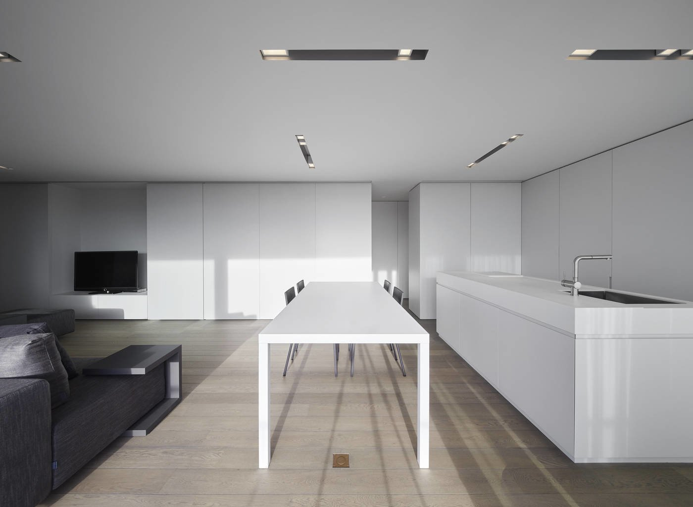 Tagged: Dining Room, Ceiling Lighting, Recessed Lighting, Table, Light Hardwood Floor, and Chair.  Photo 7 of 11 in 10 Minimalist and Monochromatic Homes in Belgium from Oostduinkerke by minus