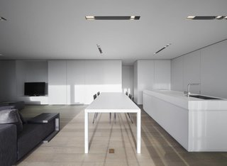 10 Minimalist and Monochromatic Homes in Belgium - Photo 6 of 10 - Oostduinkerke is a clean white interior located in West Flanders, Belgium, designed by minus.  The space is characterized by a series of strips recessed within the ceiling that conceal lighting. The main living area is open floor plan with the kitchen, dining, and living room combined into one space. The dining table is situated parallel against a large kitchen island with a full service kitchen hidden behind the cabinetry. Sliding doors provide privacy and separation between the various programs.