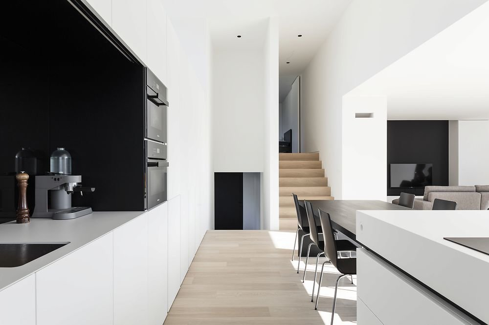 Tagged: Kitchen, White Cabinet, Light Hardwood Floor, and Wall Oven.  Photo 4 of 11 in 10 Minimalist and Monochromatic Homes in Belgium from Home DW by Francisca Hautekeete