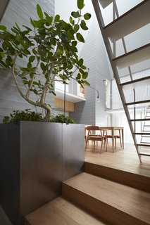 10 Ultra-Modern Homes in Japan - Photo 3 of 10 - The shared living, dining, and kitchen zone features a double-height ceiling with a large skylight at its peak.