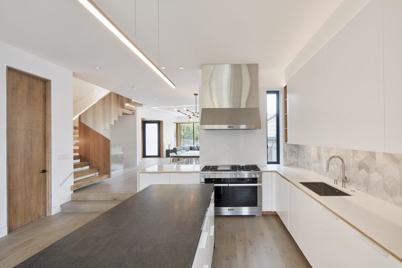 Kitchen Tagged: Kitchen, Engineered Quartz Counter, Wood Counter, White Cabinet, Ceramic Tile Backsplashe, Light Hardwood Floor, Track Lighting, Range, Range Hood, and Undermount Sink.  Noe Valley House by Leibal