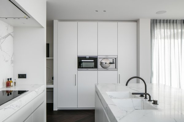 Modern home with kitchen, marble counter, marble backsplashe, recessed lighting, and wall oven. Photo 8 of Penthouse O