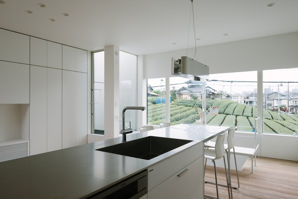 Modern home with kitchen, light hardwood floor, granite counter, and recessed lighting. Photo  of Vida