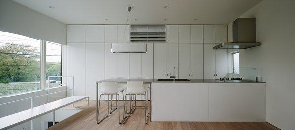 Modern home with kitchen, granite counter, white cabinet, light hardwood floor, recessed lighting, range hood, and range. Photo 8 of Vida