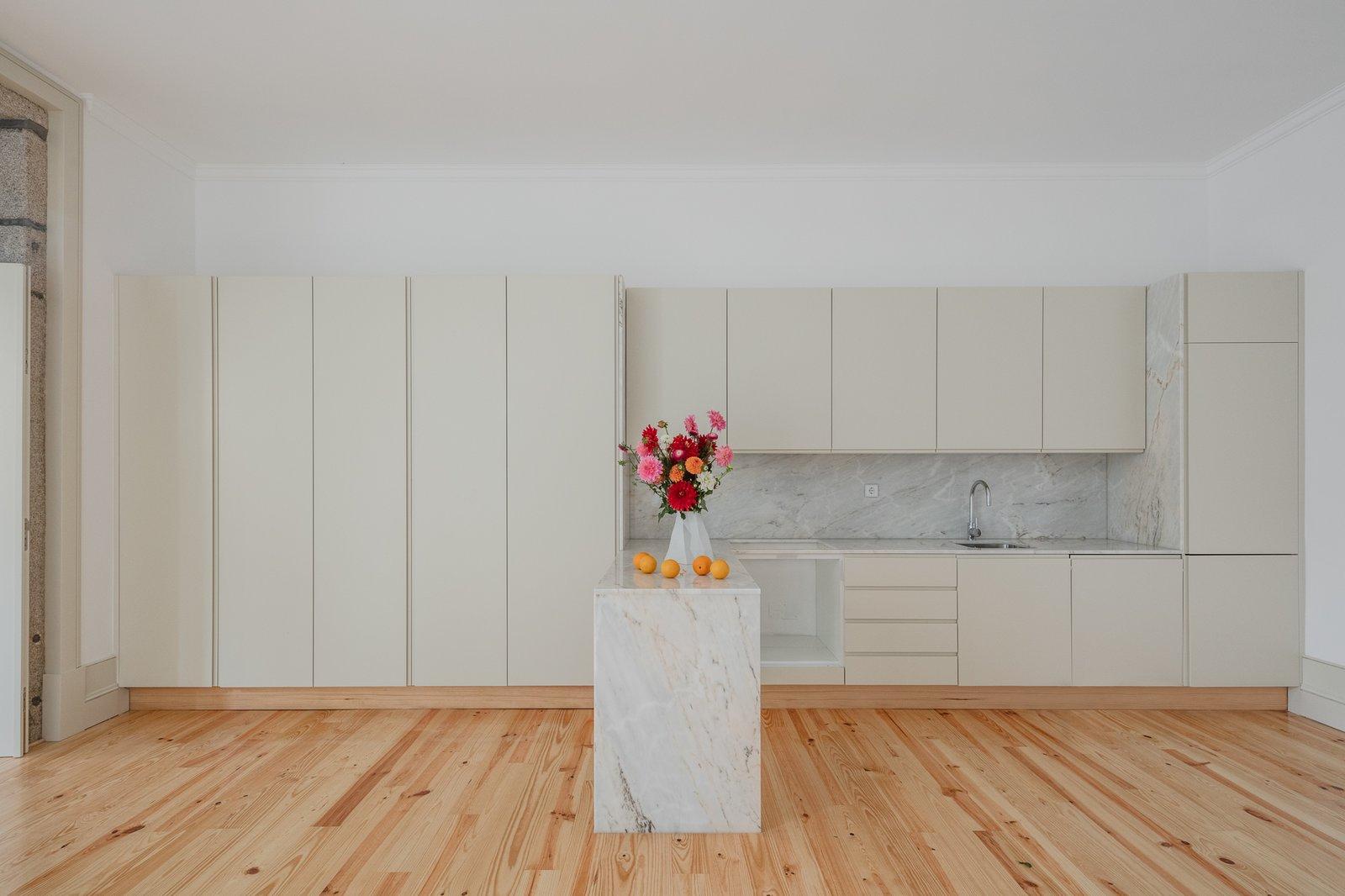 Tagged: Kitchen, Marble Counter, White Cabinet, and Light Hardwood Floor.  Rua da Boavista by Leibal