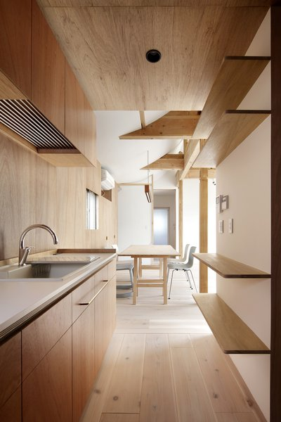Modern home with kitchen, light hardwood floor, recessed lighting, and drop in sink. Photo  of House for Four Generations