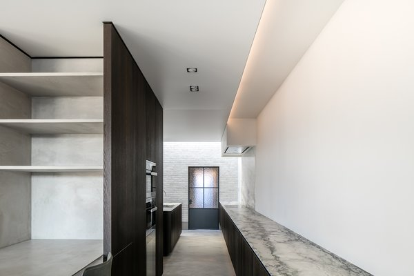 Modern home with kitchen, marble counter, light hardwood floor, ceiling lighting, and wall oven. Photo 4 of Circu House