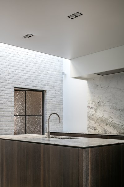 Modern home with kitchen, marble counter, marble backsplashe, ceiling lighting, recessed lighting, and undermount sink. Photo 5 of Circu House