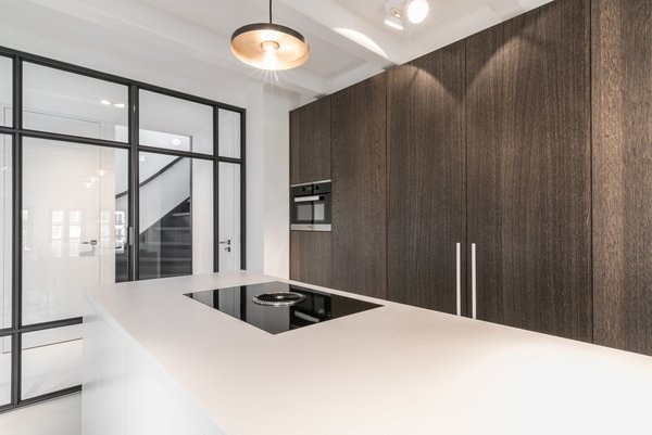 Modern home with kitchen, cooktops, wood cabinet, pendant lighting, and engineered quartz counter. Photo  of Project CC