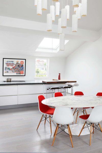 Modern home with kitchen, granite counter, white cabinet, light hardwood floor, and pendant lighting. Photo 2 of Maida Vale Apartment