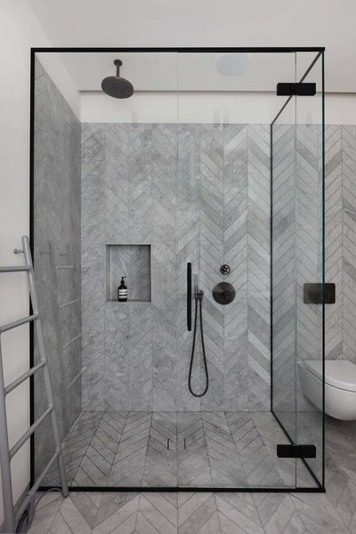 Modern home with bath room, stone counter, enclosed shower, corner shower, marble floor, one piece toilet, and stone tile wall. Photo 5 of Maida Vale Apartment