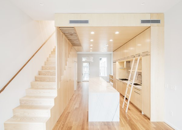 Modern home with kitchen, marble counter, wood cabinet, medium hardwood floor, marble backsplashe, and recessed lighting. Photo 9 of Wayne Street Row House