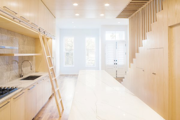 Modern home with kitchen, wood cabinet, marble counter, light hardwood floor, undermount sink, marble backsplashe, and recessed lighting. Photo 13 of Wayne Street Row House