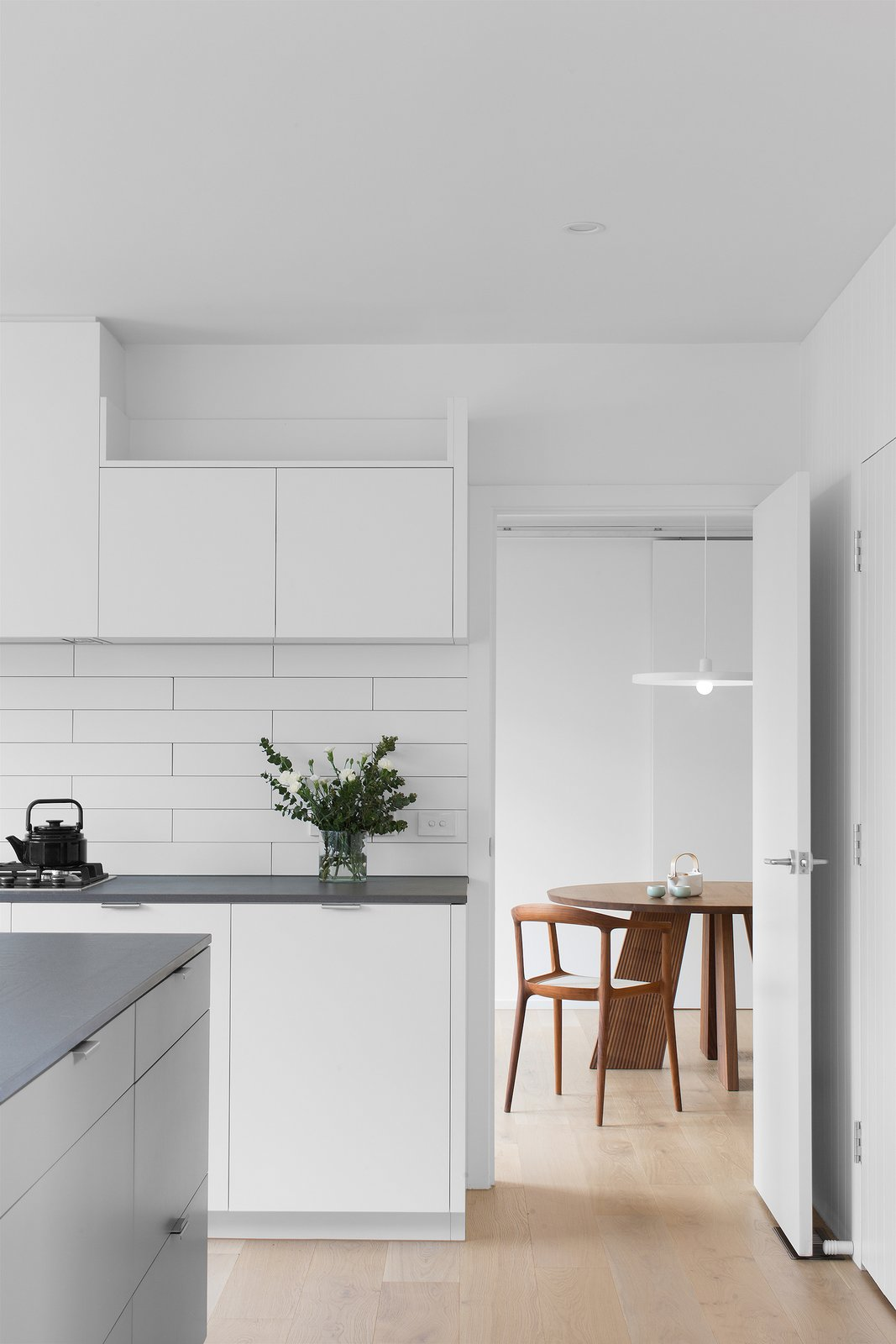 Tagged: Kitchen, Engineered Quartz Counter, White Cabinet, Light Hardwood Floor, Ceramic Tile Backsplashe, Subway Tile Backsplashe, Pendant Lighting, and Range.  Corhampton Rd Residence by Leibal