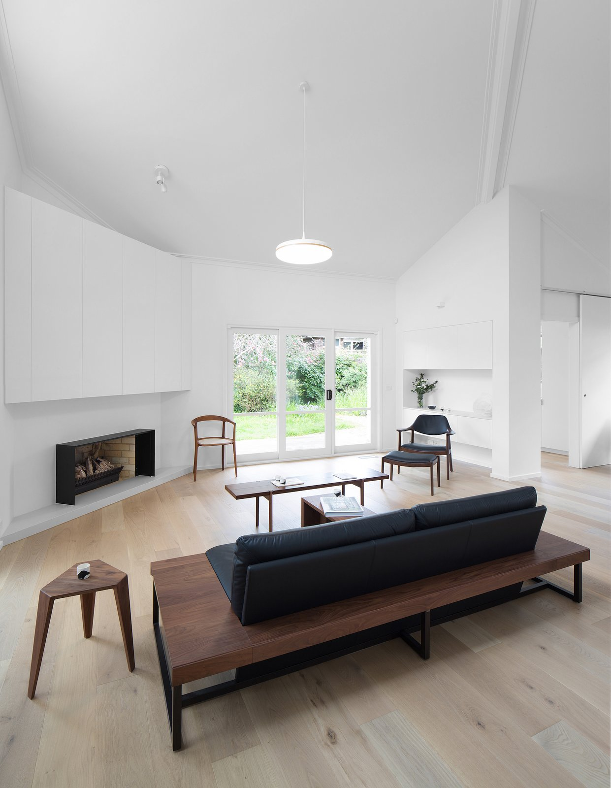 Tagged: Living Room, Pendant Lighting, Chair, Coffee Tables, Bench, Wood Burning Fireplace, and Light Hardwood Floor.  Corhampton Rd Residence by Leibal