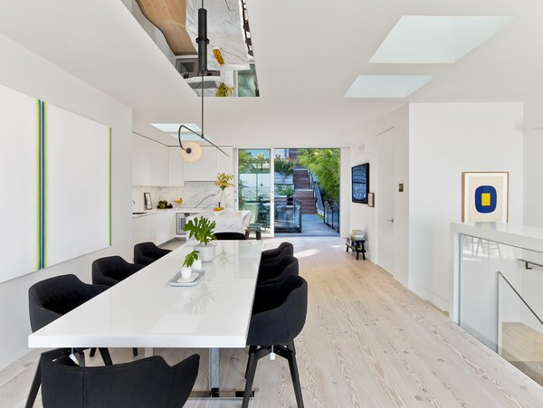 Modern home with dining room, chair, table, pendant lighting, and light hardwood floor. Photo 9 of Glen Park Residence