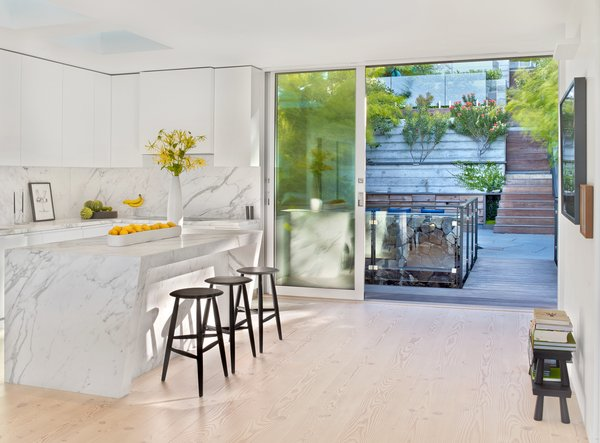 Modern home with kitchen, marble counter, white cabinet, light hardwood floor, marble backsplashe, and ceiling lighting. Photo 11 of Glen Park Residence
