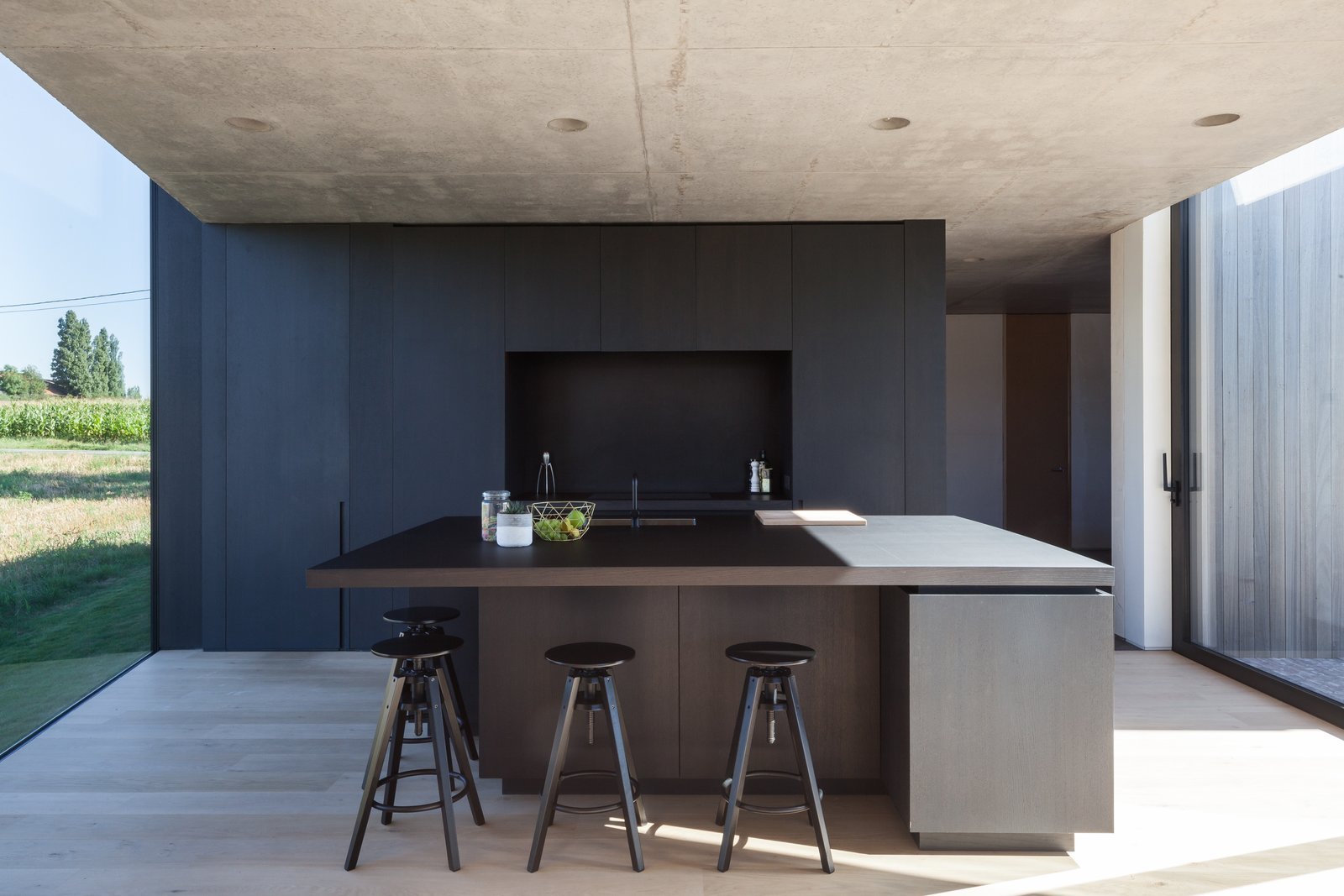 Tagged: Kitchen, Light Hardwood Floor, Wood Counter, Wood Cabinet, Recessed Lighting, and Undermount Sink.  Photo 8 of 14 in Defying traditionalism: concrete bungalow inserted in a rural Belgian landscape