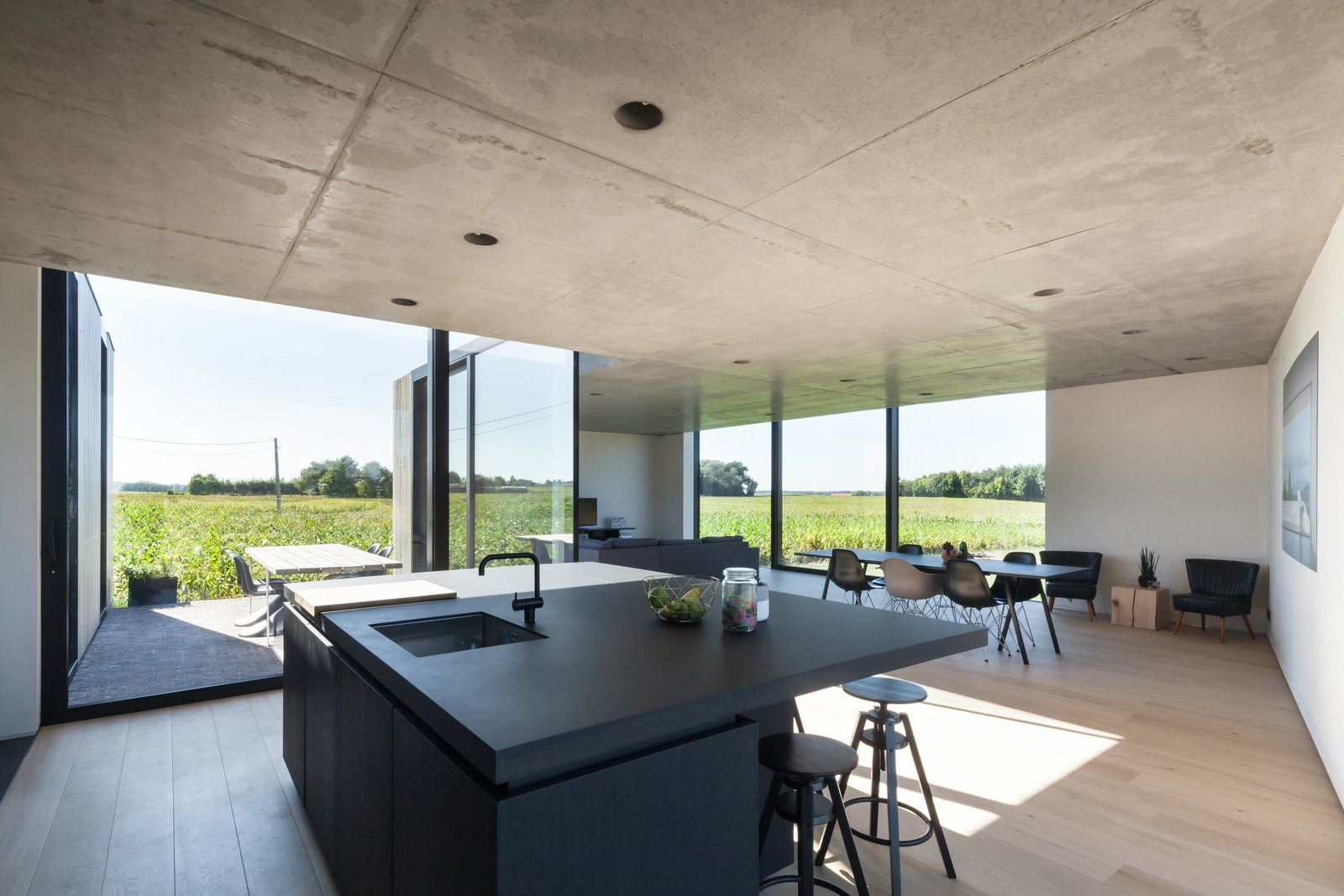 Tagged: Dining Room, Chair, Bar, Stools, Light Hardwood Floor, Table, and Recessed Lighting.  Photo 9 of 14 in Defying traditionalism: concrete bungalow inserted in a rural Belgian landscape
