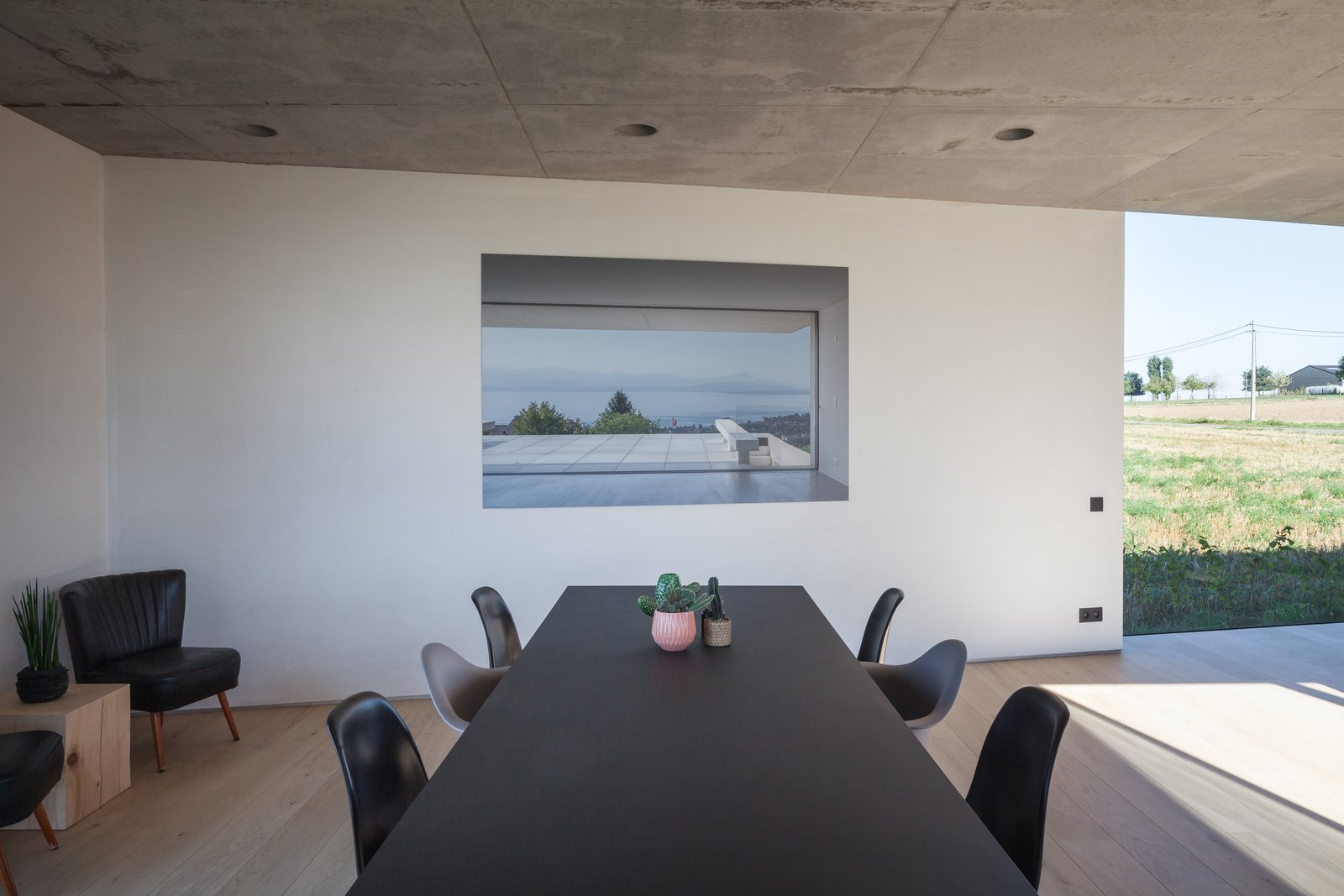 Tagged: Dining Room, Chair, Recessed Lighting, Light Hardwood Floor, and Table.  Photo 10 of 14 in Defying traditionalism: concrete bungalow inserted in a rural Belgian landscape