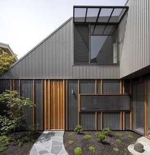 A Family Home in Australia Features a Playful Version of the Classic Pitched Roof - Photo 2 of 9 - Although the property looks like a one-story home from the street, its second level is more noticeable from the enclosed courtyard. Blackbutt vertical battens provide texture to shadowclad exterior plywood with an Onyx Quantum Aquaoil finish.