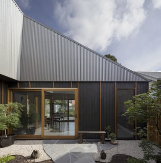 "A Family Home in Australia Features a Playful Version of the Classic Pitched Roof - Photo 3 of 9 - The owners, a couple in their 40s with a young child, wanted a home with easy access to the outdoors. ""Large sliding doors establish a fluid connection with the outdoor spaces,"" Porjazoski says, which includes a courtyard and rear garden."