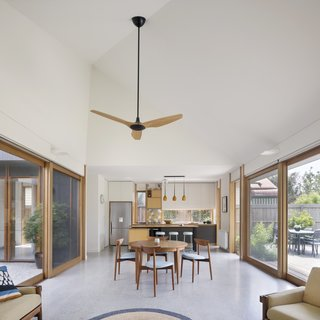 A Family Home in Australia Features a Playful Version of the Classic Pitched Roof - Photo 4 of 9 - Blackbutt window treatments and a polished-concrete floor unify the kitchen, dining, and living areas on one end of the courtyard. A Haiku ceiling fan by Big Ass Fans provides extra air.