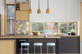 "A Family Home in Australia Features a Playful Version of the Classic Pitched Roof - Photo 5 of 9 - Gewinn pendant lights match the woodwork in the kitchen. Urban Edge's Mutina ""Tex"" Splashback tiles add a graphic element against Flexipanel cupboard doors painted in ""Parchment Matte."""