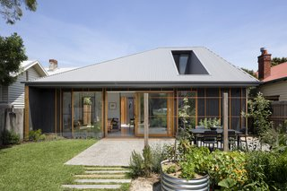 A Family Home in Australia Features a Playful Version of the Classic Pitched Roof - Photo 9 of 9 - Retaining as much of the backyard as possible was a necessity, since the homeowners enjoy gardening. An exposed aggregate concrete deck and hardwood sleeper paths bring some of the home's materials into the open space.