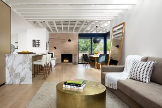 The Woman Who Grew Up in This L.A. Home Returned to Give it a Stunning Renovation - Photo 3 of 11 - Custom white oak by Contempo Floor Coverings spreads across the floor in the open living area. Malibu Market and Design supplied the metal coffee table, and the rug was purchased from Restoration Hardware.