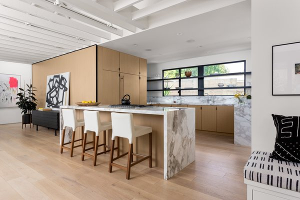 Blu Dot stools line up against calacatta gold extra countertops. The custom cabinetry was outfitted by Semihandmade with Ikea cabinet bodies.