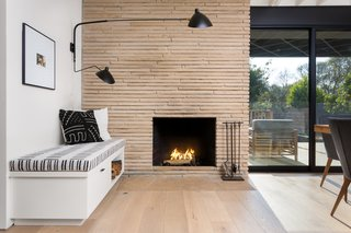 The Woman Who Grew Up in This L.A. Home Returned to Give it a Stunning Renovation - Photo 6 of 11 - The original fireplace was resurfaced using Colorado Buff Ledge stone, which offsets the black-and-white shades of the custom bench and Stilnovo sconce.