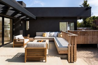 The Woman Who Grew Up in This L.A. Home Returned to Give it a Stunning Renovation - Photo 9 of 11 - The wraparound porch is enclosed in custom unfinished spruce, and match the slated look of the World Market chairs. MacInnis is a landscape designer who oversaw what was done in her own outdoor space.