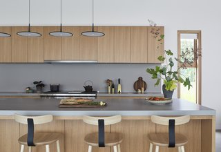This Modern Farmhouse Outside Toronto Makes Its Own Rules - Photo 2 of 11 - Caesarstone countertops are used in the kitchen. Skan pendants by Vibia hang above the island.