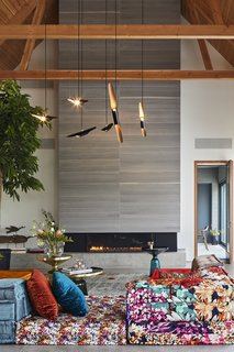"This Modern Farmhouse Outside Toronto Makes Its Own Rules - Photo 3 of 11 - ""The owner wanted some part of the house to be more cozy, and the vibrantly colored Roche Bobois sofa did the trick,"" Posno says. Bell Side Tables by Sebastian Herkner and a Coltrane suspension ceiling lamp by DelightFULL complete the look."