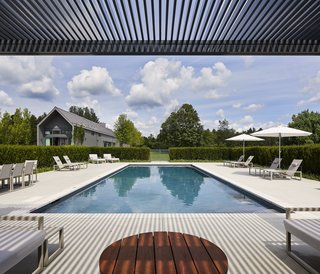 "This Modern Farmhouse Outside Toronto Makes Its Own Rules - Photo 9 of 11 -  ""It's a big property, so we had space to spread out,"" he says. ""The pool is purposefully removed from the main house in order to make it feel like a destination."" Ninix by Royal Botania furniture sits under Tucci umbrellas."