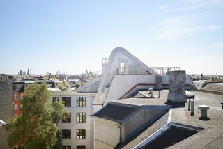 This Copenhagen Rooftop Renovation Embodies the Future of Urban Design - Photo 3 of 5 - The unique curve of the entrance's structure makes the garden stand out amid the surrounding flat roofs, and also acts as a shield from wind for the terrace and kitchen.