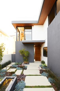 """This Renovation Will Make You Rethink the Typical Look of a California Beach House - Photo 1 of 12 - Lanscape designer Jack Kiesel opted to use succulents in the front garden for their aesthetics and low water use, a plus in Southern California. """"The sculptural quality of the succulents and color combinations pop against the smooth white stucco of the contemporary home,"""" he says."""