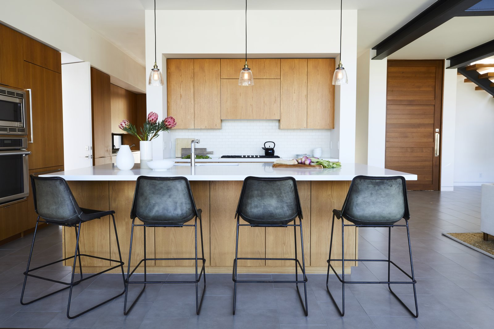 The industrial bar stools in the minimalist kitchen were purchased at ABC Home.