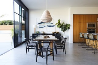 """This Renovation Will Make You Rethink the Typical Look of a California Beach House - Photo 4 of 12 - """"The owners really wanted to make sure that the furniture was inviting and interesting, but still felt like it fit the space,"""" DeSanti says. """"Martha designed a great open space, but without the furniture the space could have felt very cold."""" France and Son supplied the chairs around the custom dining table, and the chandelier was spotted at Roost."""