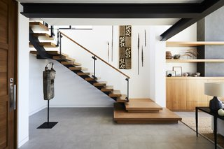 This Renovation Will Make You Rethink the Typical Look of a California Beach House - Photo 7 of 12 - The staircase was moved to be more prominently featured in the home's renovation. The owners' surrounding art collection makes it even more striking.