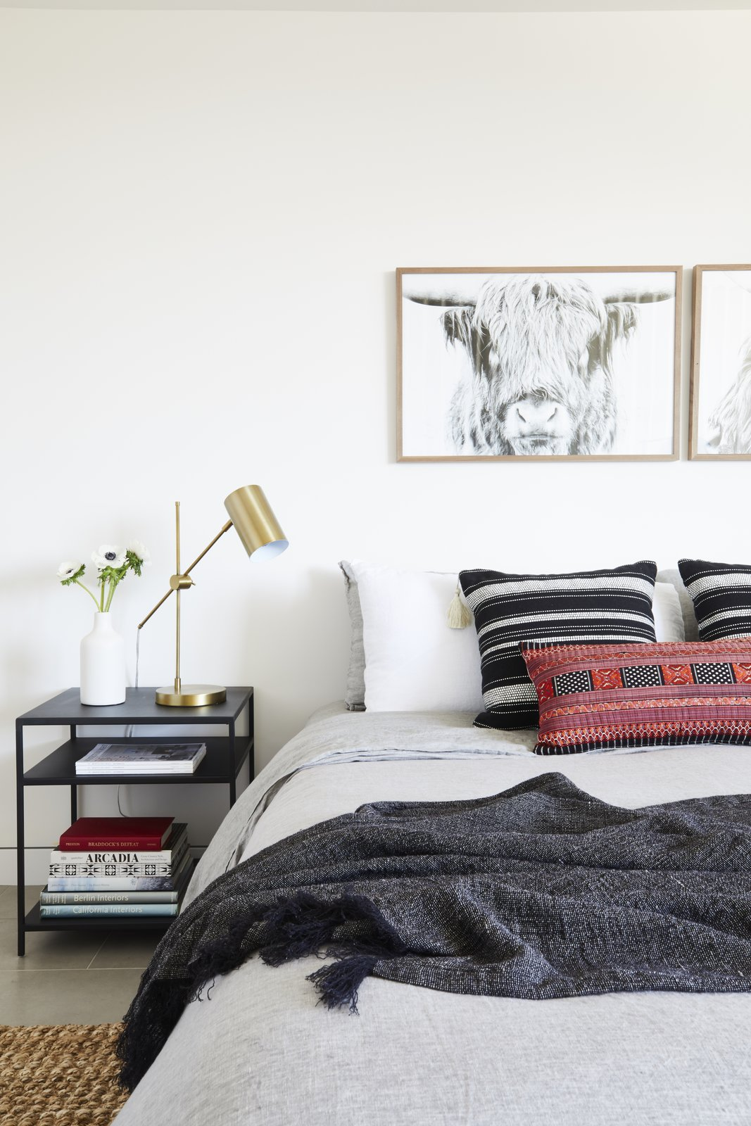 A Tim Gainey photograph of a Highland cow from Fine Art America sits above a red lumbar pillow by Amber Interiors and Restoration Hardware Bedding.