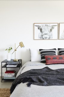 This Renovation Will Make You Rethink the Typical Look of a California Beach House - Photo 8 of 12 - A Tim Gainey photograph of a Highland cow from Fine Art America sits above a red lumbar pillow by Amber Interiors and Restoration Hardware Bedding.