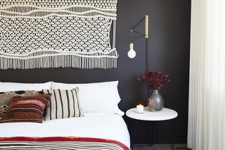 This Renovation Will Make You Rethink the Typical Look of a California Beach House - Photo 10 of 12 - In the second bedroom, a macrame wall hanging and gold sconce were found at Etsy, which matches the sentiment of the DIY nightstand. Matteo bedding pops against the Midsummer Night wall color by Benjamin Moore.