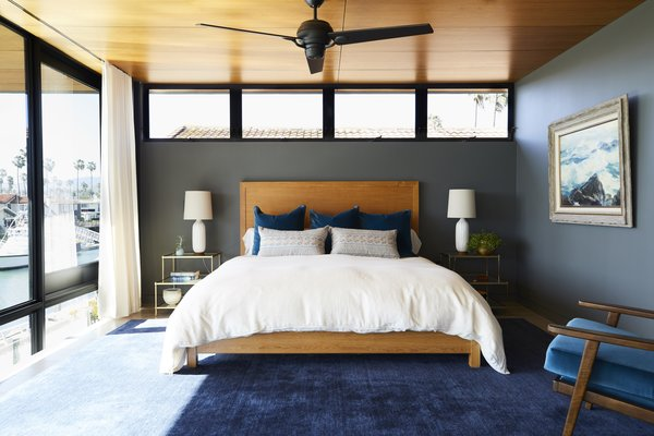 The master bedroom unites the rest of the home's shades and textures in a calm palette. The custom bed is centered above a Crate and Barrel area rug. As with most of the art in the home, the one hanging here on Benjamin Moore's