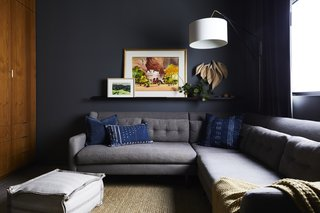 This Renovation Will Make You Rethink the Typical Look of a California Beach House - Photo 9 of 12 - In the den, the Kendall Charcoal paint shade by Benjamin Moore is matched by the equally dark shade of the West Elm sofa. Artist Laura Buchan supplied the wooden sculpture, and the floor pouf was sourced from Porch in nearby Carpinteria.