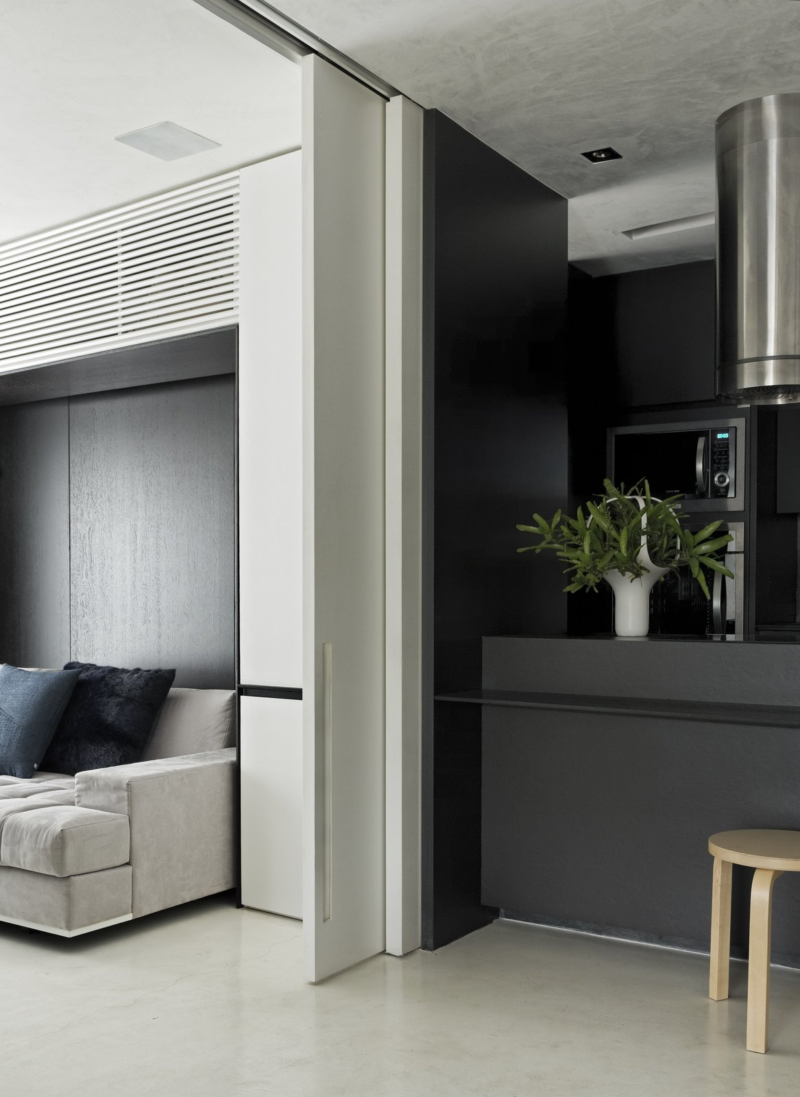 A sliding door to the guest bedroom makes this flexible area even more accessible. A burnt cement floor connects this room to the kitchen.