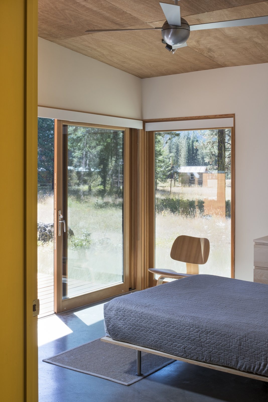 The bedroom opens out onto the deck and meadow beyond.  Lot 6 by Prentiss + Balance + Wickline Architects