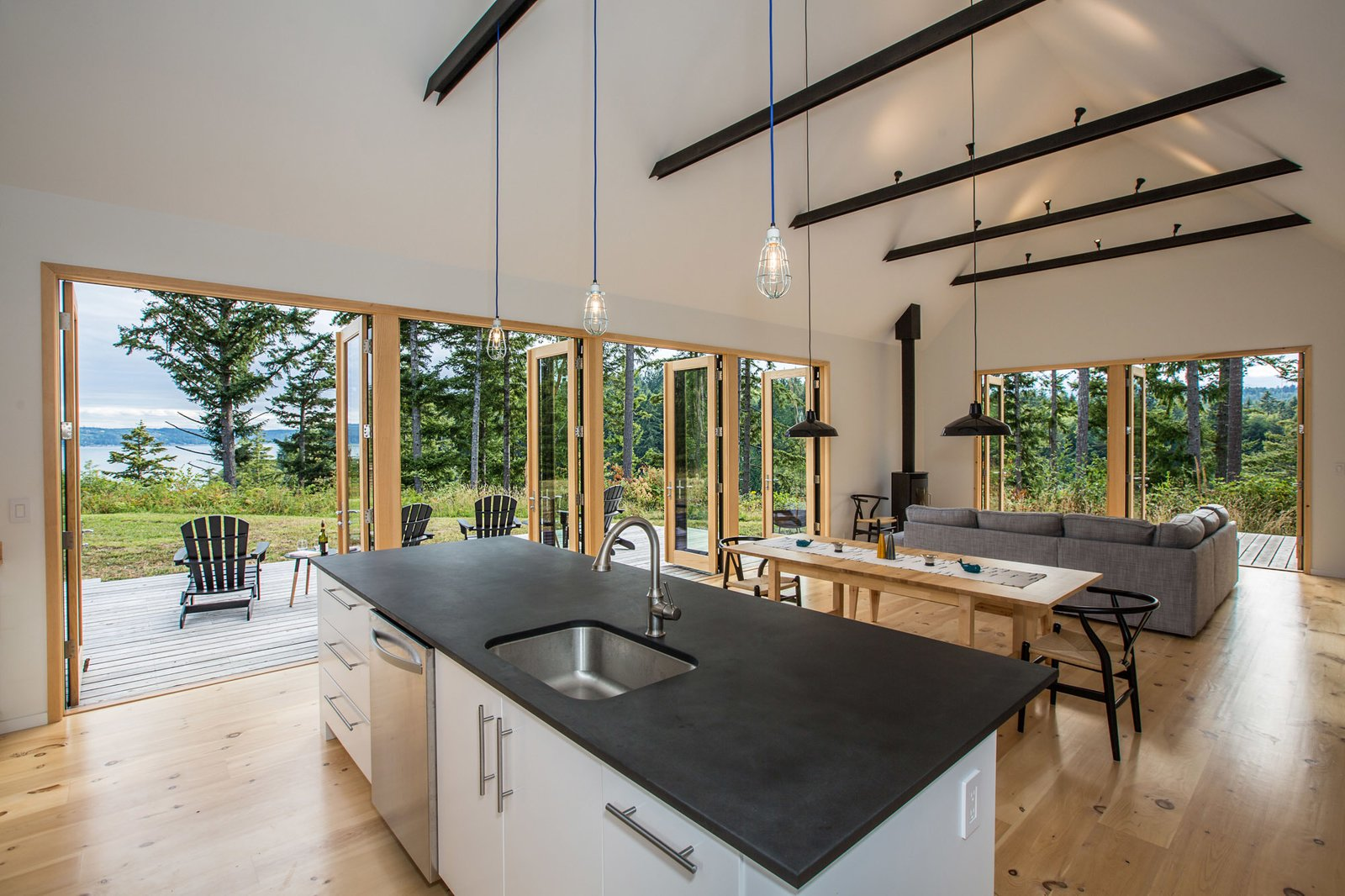 Clean, white and warm interiors are punctuated by darker accents. Tagged: Kitchen, Granite Counter, Pendant Lighting, Undermount Sink, and Light Hardwood Floor.  The Coyle by Prentiss + Balance + Wickline Architects