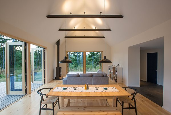 """Modern home with dining room, chair, table, track lighting, pendant lighting, and light hardwood floor. The """"great room"""" extends out to decks on two sides, creating a cozy yet expansive space for comfortable, easy living. Photo 4 of The Coyle"""